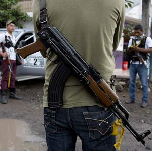 Dozens of vigilante group members, who wore white t-shirts to identify themselves, sped into a cartel-controlled Mexican town in the back of pickup trucks (AP)
