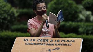 Percibald Garcia uses a microphone to read aloud children's stories amid the high-rise housing complex of Tlatelolco in Mexico City (Marco Ugarte/AP)