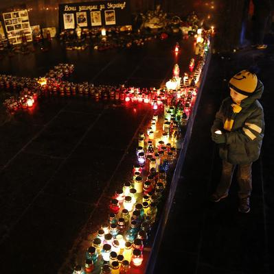 A boy in Lviv lights a candle in memory of the Ukrainian victims of clashes between police and protesters (AP)