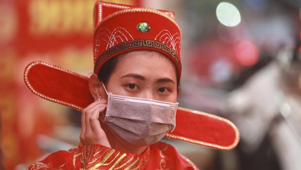 A woman in costume as the prosperity and wealth god wears a protective face mask at a gold shop in Hanoi, Vietnam (Hau Dinh/AP)