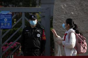 A student wearing a face mask waves to teachers as she arrives for the reopening of a primary school in Beijing (Andy Wong/AP)