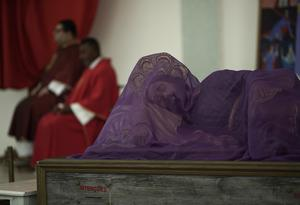 A statue of Jesus Christ is covered with a purple veil as priests attend the Passion of Christ Mass broadcast on a live video stream inside the empty Sao Jose da Lagoa Catholic church in Rio de Janeiro, Brazil, on Good Friday, April 10, 2020. (AP Photo/Silvia Izquierdo)