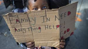 A child in New Orleans begging for money in the wake of the coronavirus crisis (David Grunfeld/The Advocate via AP)