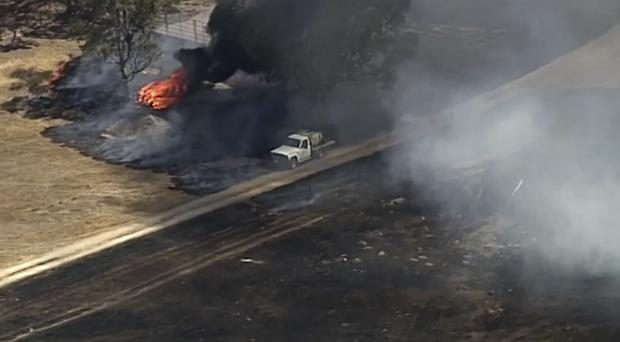 In this image made from video, an aerial scene shows a truck driving near fire burning in Harrogate, South Australia, Wednesday, Dec. 25, 2019. South Australia state, which last week had dozens of homes destroyed after wildfires flared in catastrophic conditions, is bracing for a return of extreme temperatures, with Adelaide, the state capital, expected to reach 41 C (106 F) on Saturday.(Australian Broadcasting Corporation, Channel 7, Channel 9 via AP)