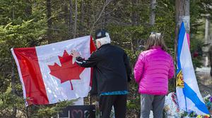 A couple place a flag at a memorial in Portapique, Nova Scotia, following Saturday's shooting rampage. (Andrew Vaughan/The Canadian Press via AP)