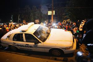 A police squad car is turned over by demonstrators during riots in Ferguson, Missouri
