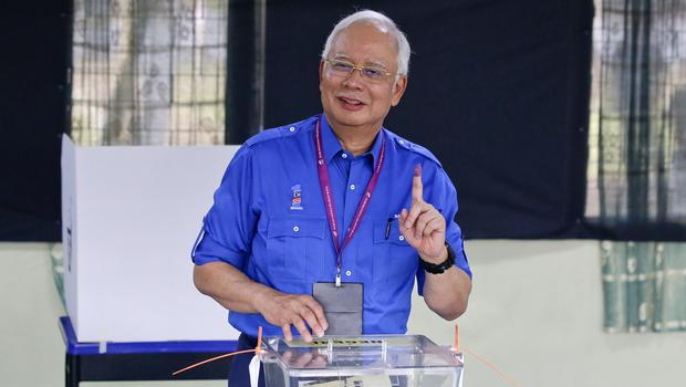 Malaysian Prime Minister Najib Razak smiles after voting in the general election (AP)