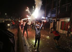 Indonesian youths light firecrackers and flares as they celebrate the end of the fasting month of Ramadan (Dita Alangkara/AP)