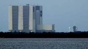 With the Vehicle Assembly Building pictured in the foreground, the SpaceX Falcon 9, with the Dragon capsule on top of the rocket, is seen on Launch Pad 39-A (Charlie Riedel/AP)