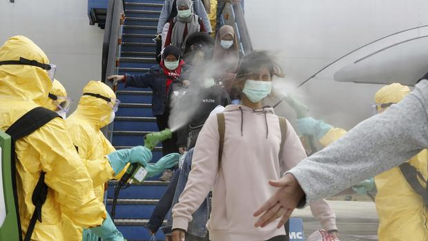 Indonesians who arrived from Wuhan are sprayed with antiseptic at Hang Nadim Airport in Batam (Indonesian Foreign Ministry/AP)