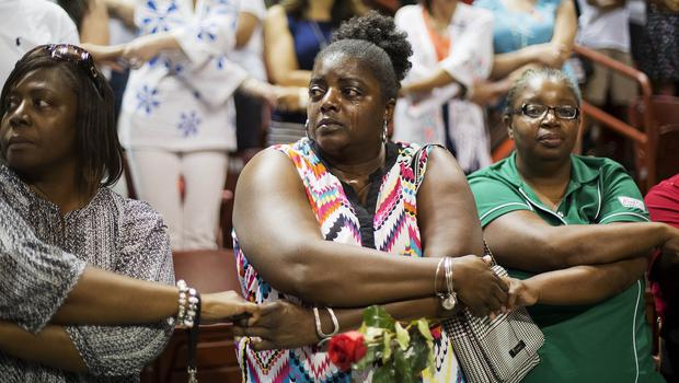 Mourners hold hands during the singing of We Shall Overcome at a memorial service for the victims of the shooting at Emanuel AME Church in Charleston (AP)