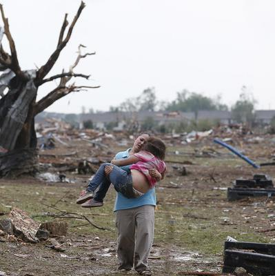 A woman carries her child through a field near the collapsed Plaza Towers Elementary School in Moore, Oklahoma (AP, Sue Ogrocki)