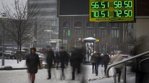 People walk past a sign advertising currency exchange rates in Moscow (AP)