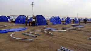 Workers set up a camp for displaced Iraqis in Khazer (AP)