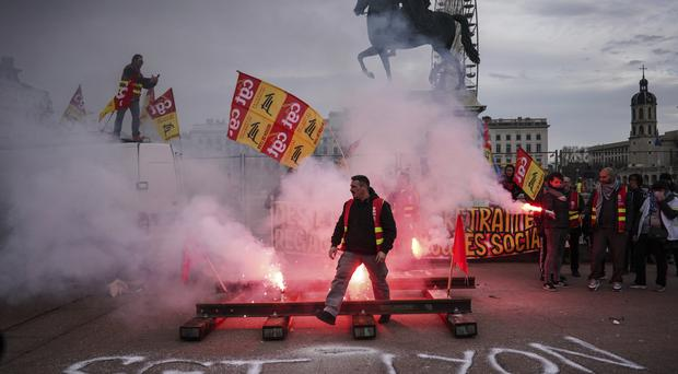 A protester passes by flares during a demonstration in Lyon (AP)