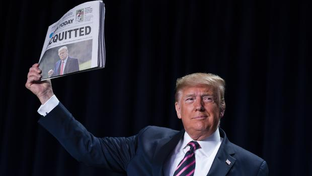 US President Donald Trump holds up a newspaper with a headline that reads 'Acquitted' (Evan Vucci/AP)