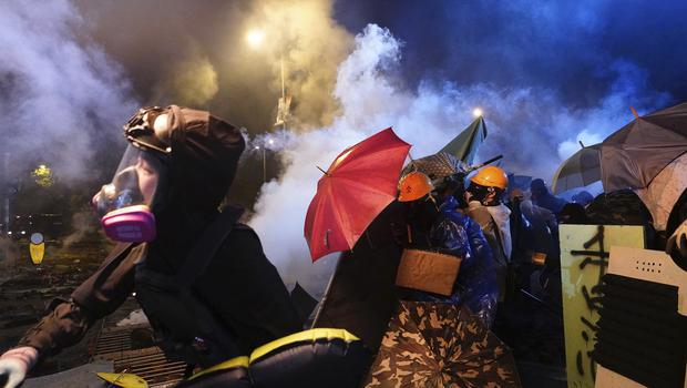 Protesters react as police fire tear gas (Vincent Yu/AP)