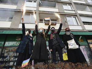 Polish protesters hold sparklers and a rainbow flag during anti-government protests (Czarek Sokolowski/AP)