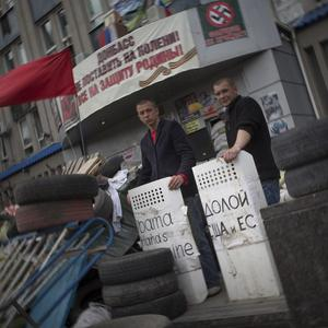 Pro-Russian activists hold police shields with the words 'Obama, hands off Ukraine!' as they guard the barricade at the Ukrainian regional office of the Security Service in Luhansk (AP)
