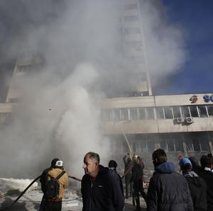 Bosnian protesters help firefighters to extinguish a fire inside a government building in Tuzla (AP)