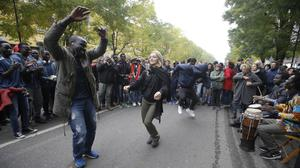 Migrants and citizens dance outside the Montello barrack, in Milan, Italy (AP)