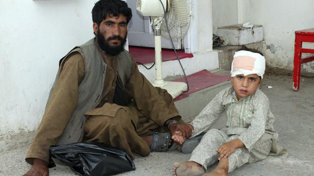 A boy who was injured boy in a deadly attack on a market sits on the ground at a hospital in Afghanistan's Helmand province (Abdul Khaliq/AP)