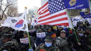 War veterans hold flags during a rally denouncing the attack on the US ambassador to South Korea Mark Lippert in downtown Seoul (AP)