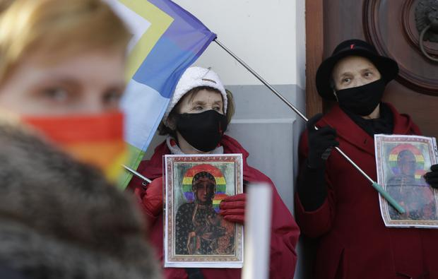 Activists gather outside court with copies of the poster (Czarek Sokolowski/AP)