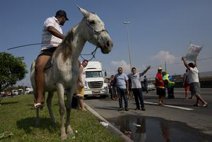 Lorry driver Douglas Ramos rides his horse alongside striking colleagues (Silvia Izquierdo/AP)