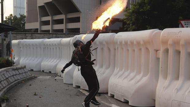 An anti-government protester throws a Molotov cocktail during a demonstration near the Central Government Complex (Kin Cheung/AP)
