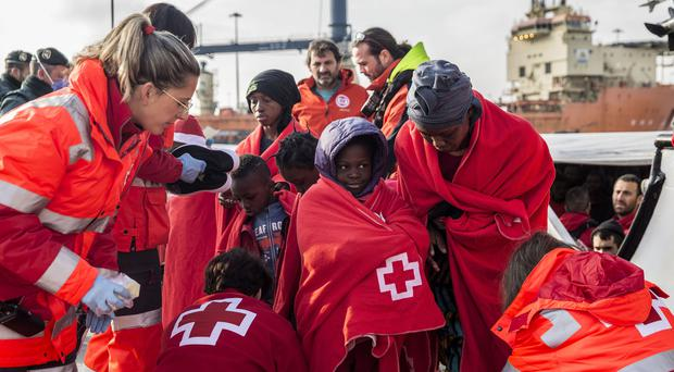 A young migrant is helped from the Spanish aid boat Proactiva Open Arms (Olmo Calvo/AP)
