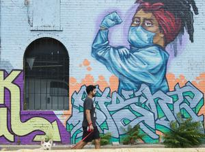 A man walks past a mural that pays tribute to healthcare workers in Toronto (Nathan Denette/The Canadian Press via AP)