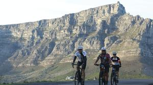Cyclists exercise against a backdrop of Table Mountain in Cape Town (Nardus Engelbrecht/AP)
