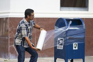 A United State Postal Service employee covers a post box with plastic wrap after removing its contents in anticipation of Hurricane Laura (Mark Mulligan/Houston Chronicle via AP)