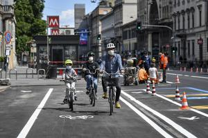 A family tries the new cycle path being prepared in central Milan's Corso Venezia, Italy (Claudio Furlan/LaPresse via AP)