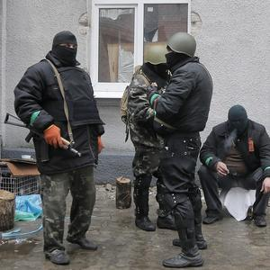 Pro-Russian gunmen stand guard at a seized police station in the eastern Ukrainian town of Slovyansk. (AP)