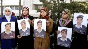 Anwar al-Tarawneh, centre, the wife of Jordanian pilot Lt Muath al-Kaseasbeh, campaigns for his release (AP)