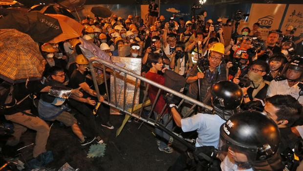 Pro-democracy protesters scuffle with police officers on the main road outside the government headquarters in Hong Kong (AP)
