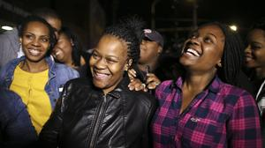 Family members surround Keisha Gaither, second from left, mother of kidnapping victim Carlesha Freeland-Gaither, as they celebrate her safe return (AP)