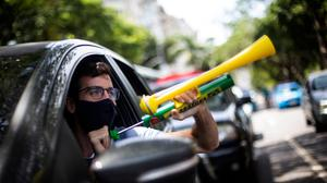 """A demonstrator shouts """"Out Bolsonaro"""" while using a noisemaker during a caravan to protest the government's handling of the COVID-19 pandemic and demand the impeachment of Brazilian President Jair Bolsonaro in Rio de Janeiro, Brazil, Saturday, Jan. 23, 2021. (AP Photo/Bruna Prado)"""