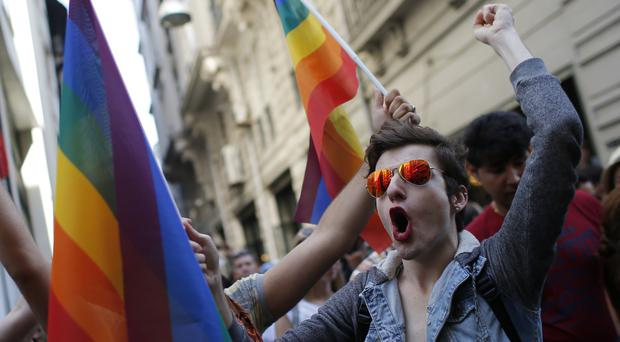 Participants of a 2015 Pride Week event in Istanbul chant slogans after police used a water canon to disperse them