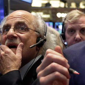 Trader Peter Tuchman, left, working on the floor of the New York Stock Exchange as markets fell worldwide (AP)