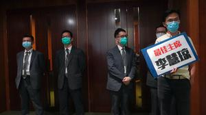 """Pro-democracy lawmaker Eddie Chu, right, holds a placard reading """"Best Chairperson, Starry Lee"""" as he stands outside the chamber of Legislative Council Complex after he was ejected minutes after a second-day legislative debate in Hong Kong (Vincent Yu/AP)"""
