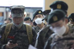 Military soldiers wearing face masks line up to buy train tickets in Seoul, South Korea (Ahn Young-joon/AP)