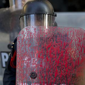 A police officer's shield is covered in red paint that was thrown by protesters marking the anniversary of the Tlatelolco massacre in Mexico City (AP)