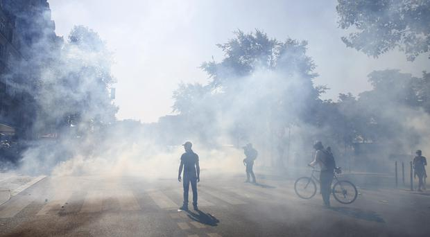 Protesters seen among tear gas during one demonstration (AP)