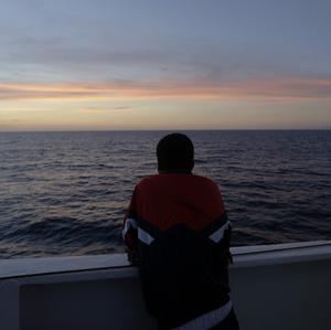 Amsa, 16, a migrant from Somalia, watches the sunset as he leaves the Sicilian island of Lampedusa (AP)
