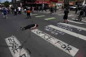 A woman lies in the street as protesters gather near the site of George Floyd's arrest (AP/Jim Mone)