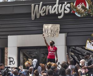 People hold a rally at Wendy's on University Avenue following the death of Rayshard Brooks (Steve Schaefer/Atlanta Journal-Constitution via AP)