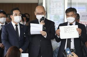 Officials from the Seoul Metropolitan Government show a note from Park Won-soon (Im Hwa-young/Yonhap/AP)